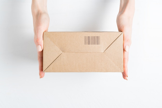 Rechthoekige kartonnen doos met barcode in vrouwelijke handen. bovenaanzicht,