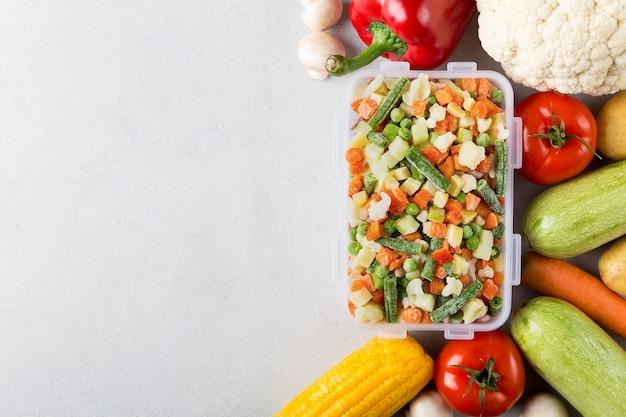 Rechthoekige plastic bak met mix van diepvriesgroenten plat leggen met kopie ruimte en vers voedsel