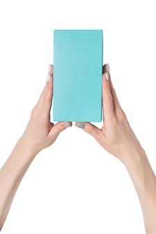 Rechthoekige turquoise doos in vrouwelijke handen. bovenaanzicht. isoleren