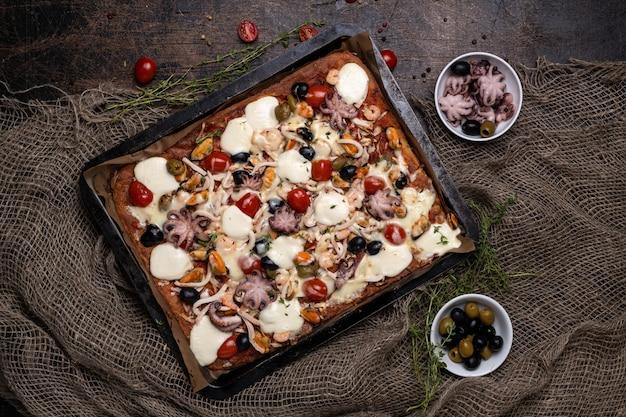 Rechthoekige zelfgemaakte zeevruchtenpizza met inktvis, garnalen, mosselen en inktvis op een donkere houten achtergrond. close-up en bovenaanzicht.