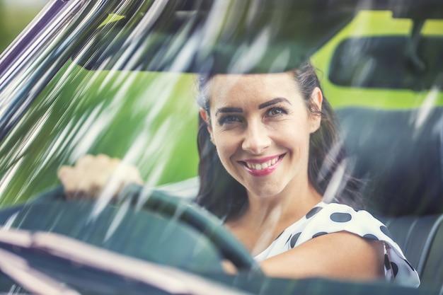 Rechts rijdende vrouw zit achter het stuur van een auto en glimlacht door de voorruit in de camera.