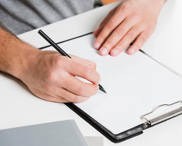 Rechtshandige persoon die op leeg papier schrijft