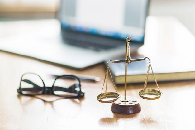 Rechtvaardigheidsschaal en bril op houten bureau in rechtszaal