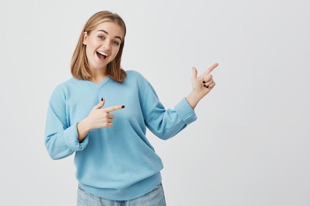 Reclame concept. gelukkige jonge europese vrouw met blond haar en blauwe kleren, die zich tegen grijze concrete muurachtergrond bevinden met exemplaarruimte voor uw informatie of promotionele inhoud