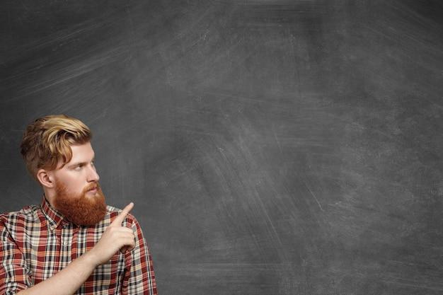 Reclame concept. knappe jonge bebaarde man in casual geruit overhemd kijken naar leeg schoolbord en zijn wijsvinger wijzend op kopie ruimte voor uw tekst of promotionele inhoud.