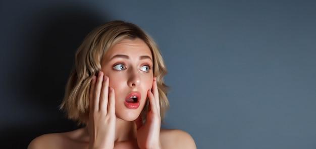 Reclame concept van verrassing en angst. close-up portret mooie jonge vrouw bang met haar handen op haar gezicht tegen donkere geïsoleerde achtergrond. vrouwelijke actrice emotie litteken. ruimte voor site kopiëren