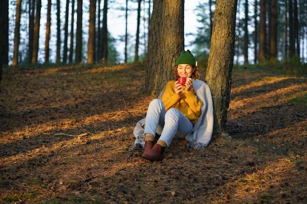 Recreatie in de natuur, een gelukkige vrouw zit onder de boom in het herfstbos en drinkt hete thee terwijl ze geniet van de zonsondergang