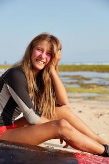 Recreatie, sport en lifestyle concept. vrolijk meisje houdt van surfen, heeft rust na een reis