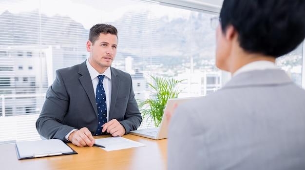 Recruiter die de kandidaat controleert tijdens een sollicitatiegesprek