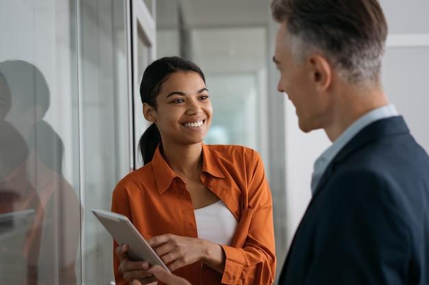 Recruiter met behulp van digitale tablet luisteren naar kandidaat tijdens sollicitatiegesprek.