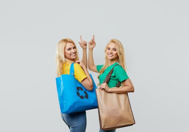 Recycle concept. jonge vrouwen in vrijetijdskleding houden ecologische gerecyclede boodschappentassen vast en wijzen naar de lege ruimte voor tekst.
