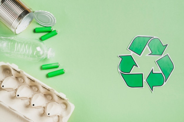 Recycle pictogram met afvalproducten op groene achtergrond