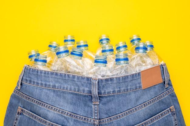 Recycle technologie van plastic fles om kleding te maken. bovenaanzicht oude fles water en blauwe korte spijkerbroek