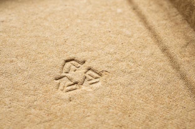Recycle teken op bruine kartondocument textuurachtergrond