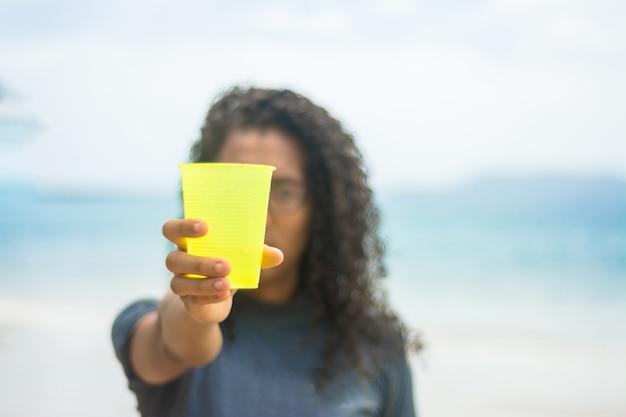 Recycleer, pak plastic beker op het strand