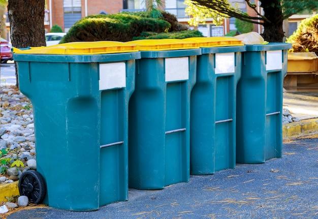 Recyclingbakken bij een aparte recycling-vuilnisbak voor afvalscheiding bij de ingang van het huis.