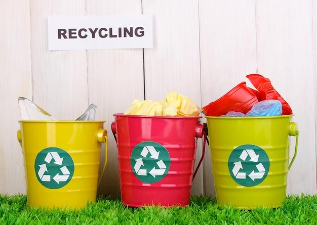 Recyclingbakken op groen gras dichtbij houten omheining