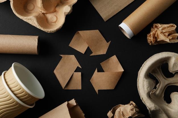 Recyclingsteken op zwarte achtergrond met verschillend afval, hoogste mening