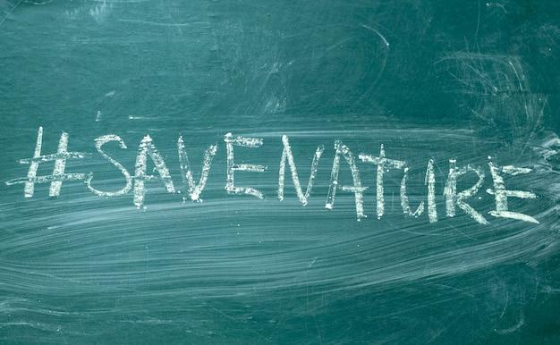 Red de aard hashtag het met de hand geschreven met wit krijt op een groen bord
