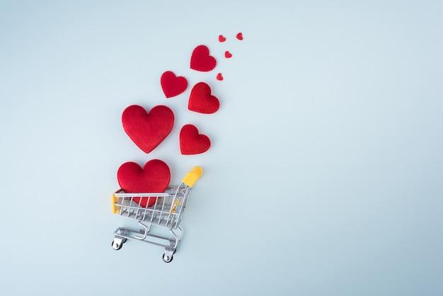 Red heart shape met winkelwagentje op blauwe achtergrond voor liefde bruiloft en valentijnsdag.