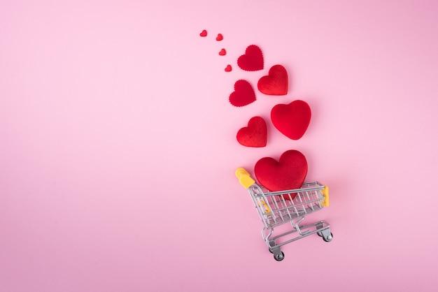 Red heart shape met winkelwagentje op roze achtergrond voor liefde bruiloft en valentijnsdag.