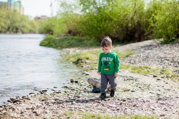 Red het milieuconcept, een kleine jongen die afval en plastic flessen op het strand verzamelt om in de prullenbak te dumpen.