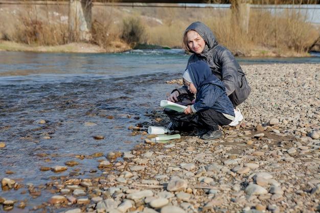Red het milieuconcept, een kleine jongen en zijn moeder verzamelen afval en plastic flessen op het strand om in de prullenbak te dumpen.
