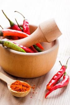 Red hot chili peper in houten vijzel op tafel