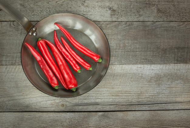 Red hot chili peppers en pan op vintage houten bord. bovenaanzicht met kopie ruimte.