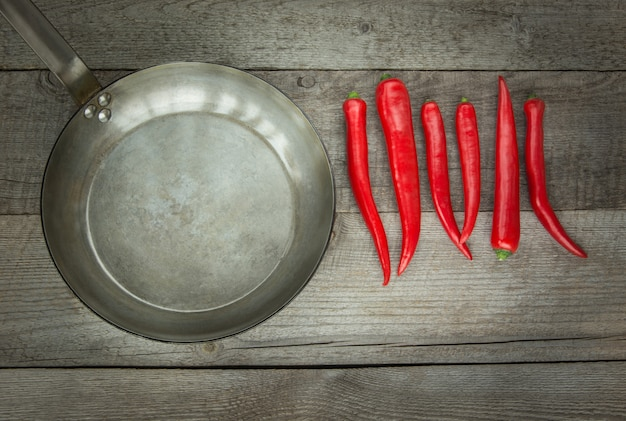 Red hot chili peppers en pan op vintage houten bord. bovenaanzicht.