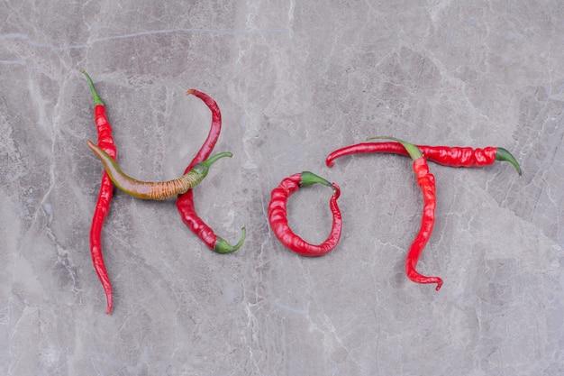 Red hot chili peppers geïsoleerd op marmeren oppervlak