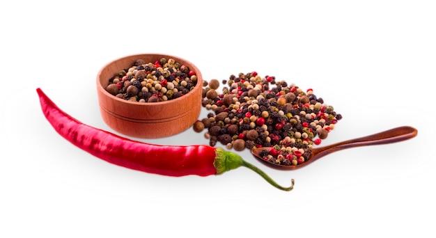 Red hot chili peppers met houten maatlepel en cup met colore peper