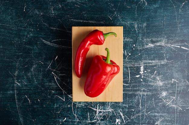Red hot chili peppers op een houten bord, bovenaanzicht.