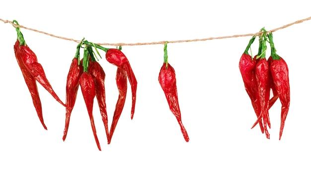 Red hot chili peppers opknoping op een drie touwen geïsoleerd op de witte achtergrond