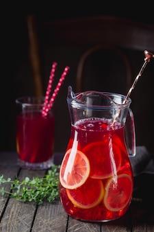 Red iced limonade met gesneden verse citroenen in een kruik op donkere houten