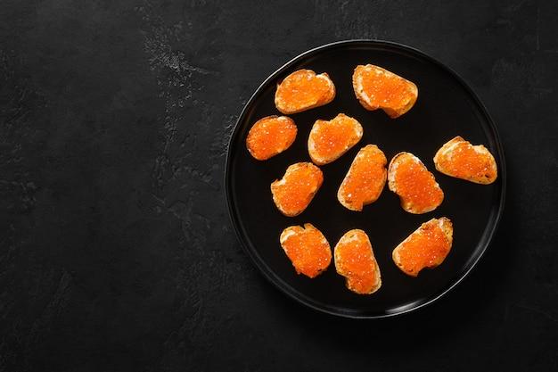 Red salmon caviar canapé voor feest op zwarte achtergrond. feestelijk vakantiediner.