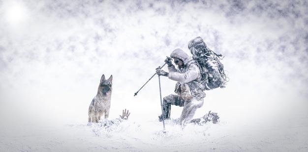 Redden in de sneeuw met duitse herdershond en brandweerman-bergbeklimmer