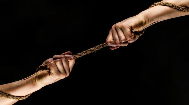 Redding, hulp, helpend gebaar of handen. conflict, touwtrekken. twee handen, helpende hand, arm, vriendschap.