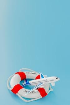 Reddingsboei en model van vliegtuig op blauwe achtergrond. zomer of vakantie concept. ruimte kopiëren.