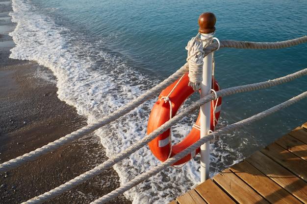 Reddingsboei met een touw ligt aan de rand van water op het strand