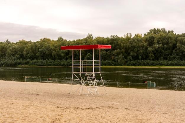 Reddingstoren en omheind strand aan de rivier.