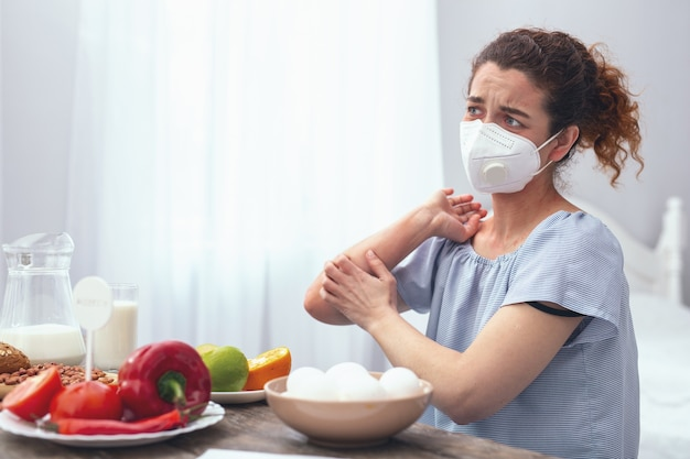 Reden in eten. adolescente dame die bezorgd kijkt en last heeft van allergische jeuk aan haar elleboog, veroorzaakt door voedselallergieën