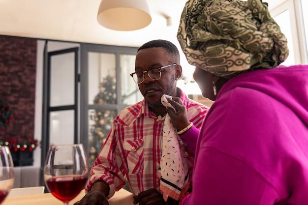 Reden om te vieren. aardige, vrolijke man die wijn in glazen giet terwijl hij een reden heeft om te vieren