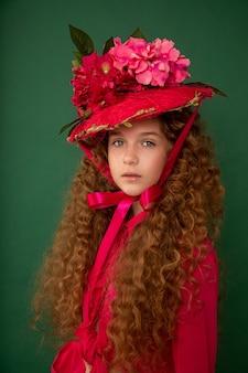 Redhair mooi meisje met krullende afro krullen in fel roze jurk op groene achtergrond.