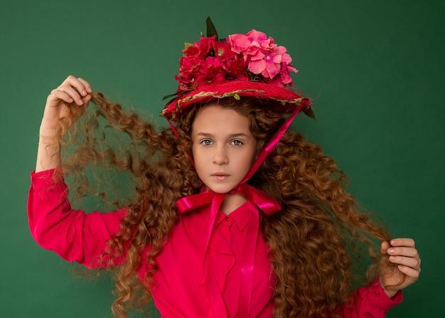 Redhair mooi meisje met krullende afro krullen in helder roze blouse op groene achtergrond.