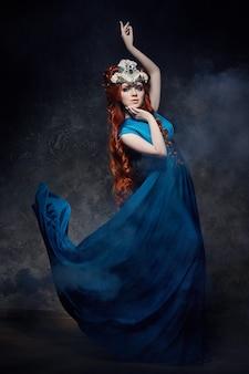 Redhead fabelachtig meisje ziet eruit, blauwe lange jurk make-up