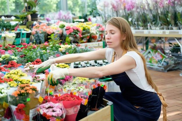 Redhead jonge vrouwenarbeider in de serre van de installatiemarkt zorgt voor bloemen