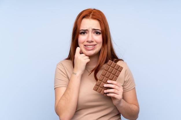 Redhead tienermeisje over blauw die een chocoladetablet nemen en twijfels hebben