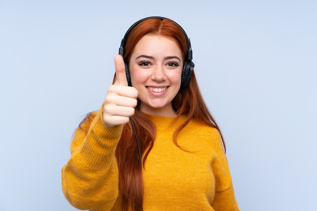 Redhead tienervrouw die aan muziek en met omhoog duim luisteren