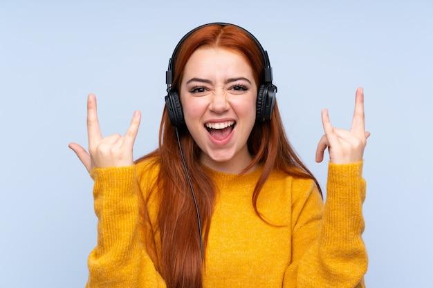 Redhead tienervrouw die aan muziek luisteren die rotsgebaar maken